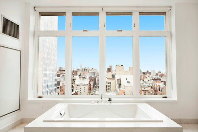 Rihanna's $14 Million Dollar NYC Penthouse nyc penthouse Rihanna's $14 Million Dollar NYC Penthouse new york nyc penthouse master bath city view bathroom skyline new york design agenda all white tub multi million dollar real estate listing